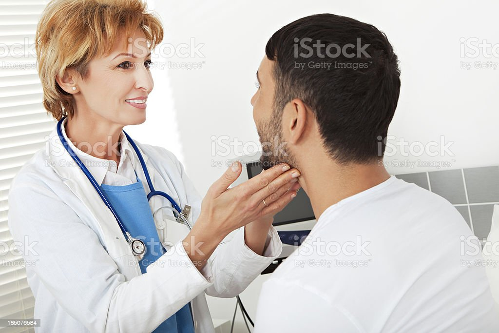Female doctor examining a young man stock photo