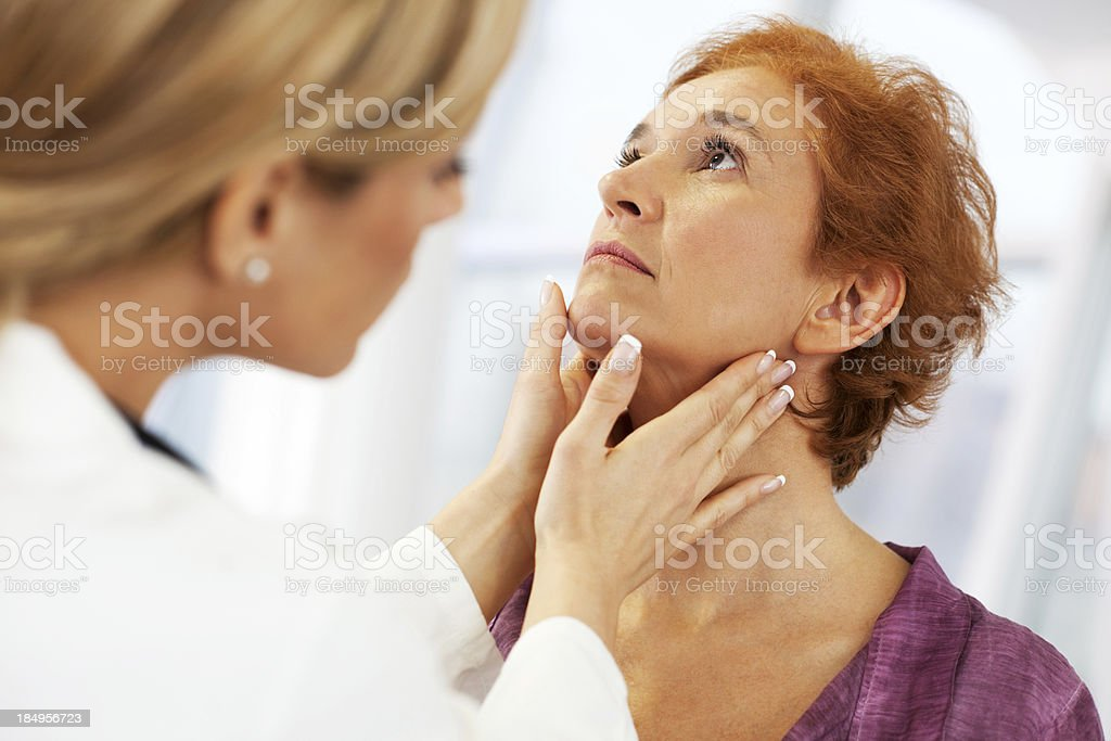 Female doctor examining her patient. stock photo