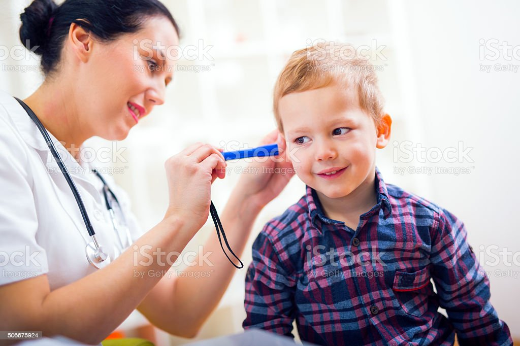 Female doctor examining little child boy. stock photo