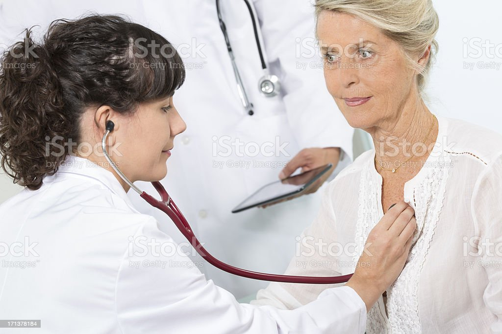 female doctor examining with stethoscope the lung of senior patient stock photo