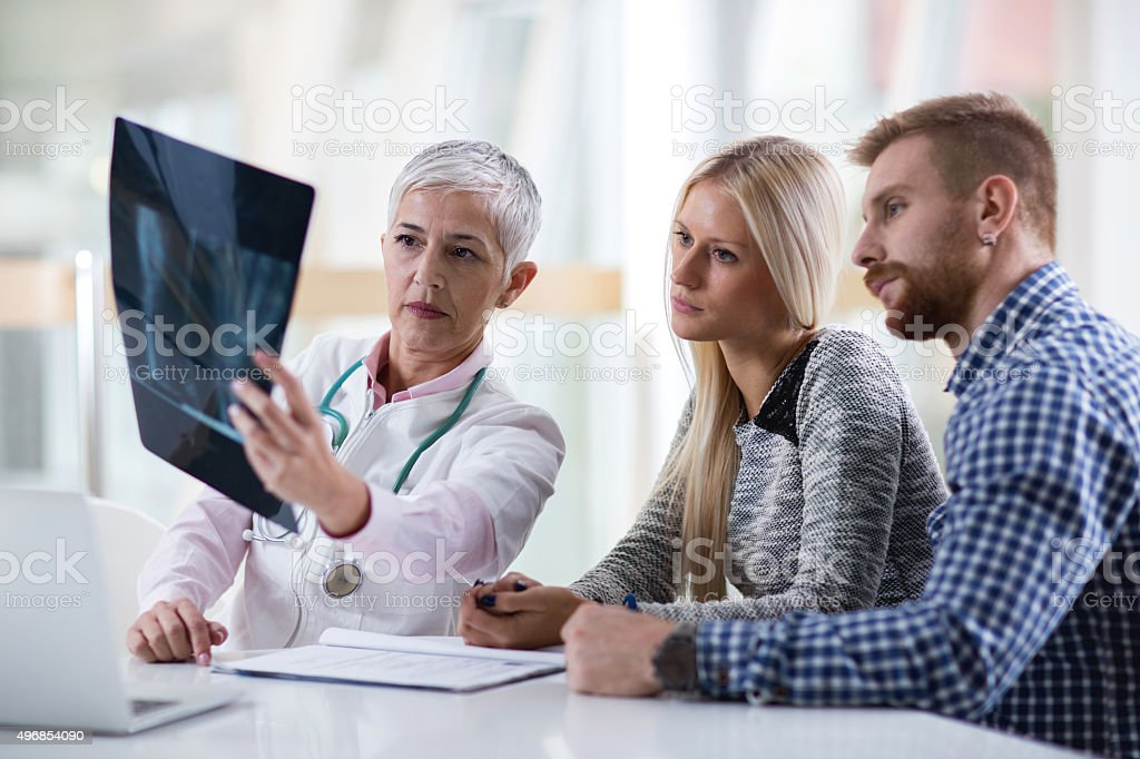 Female doctor examining X-ray image with young couple. stock photo
