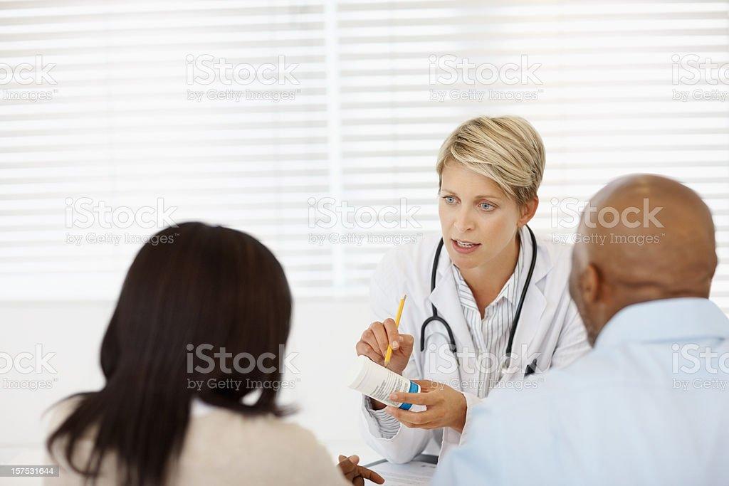 Female doctor explaining medication to a couple royalty-free stock photo