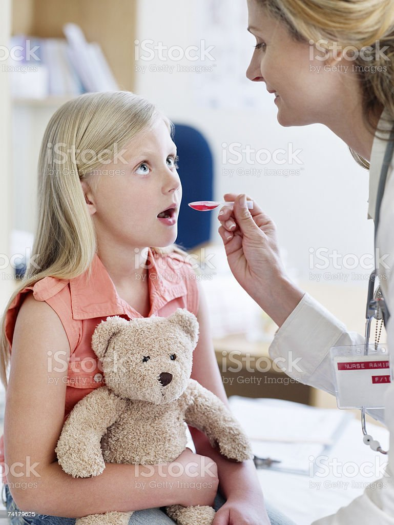 Female doctor giving medicine to girl with teddy bear royalty-free stock photo