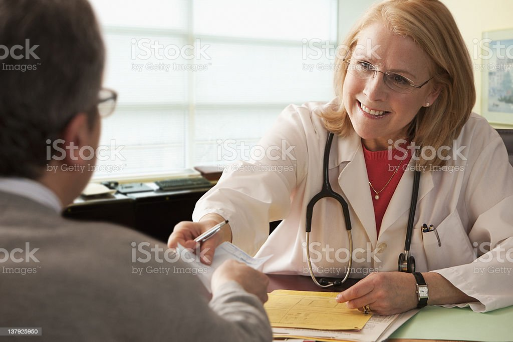 Female doctor giving prescription to male patient royalty-free stock photo