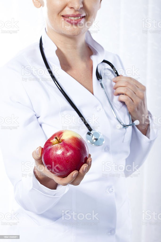 Female doctor giving red apple royalty-free stock photo