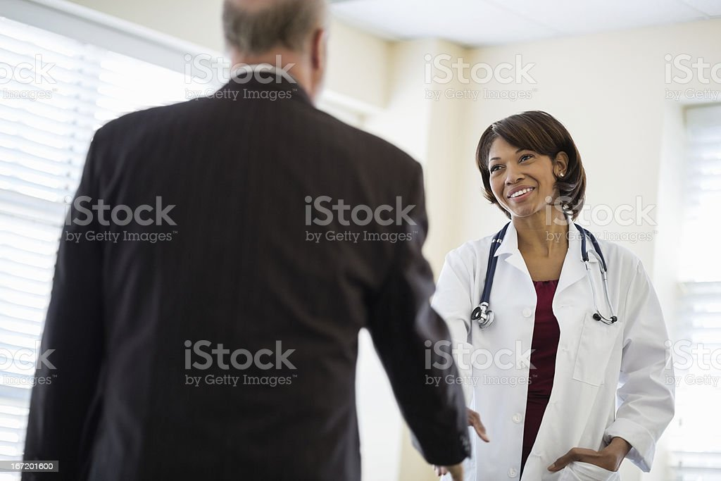 Female Doctor Greeting Businessman In Clinic royalty-free stock photo