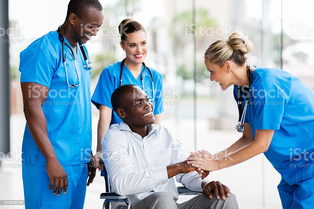 female doctor greeting disabled patient stock photo