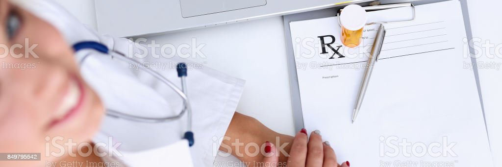 Female doctor hand hold jar of pills and write prescription stock photo