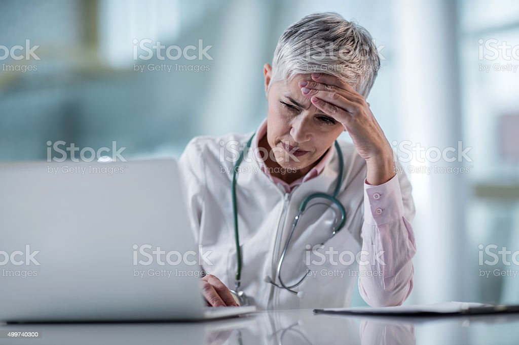 Female doctor having a headache while being at doctor's office. stock photo