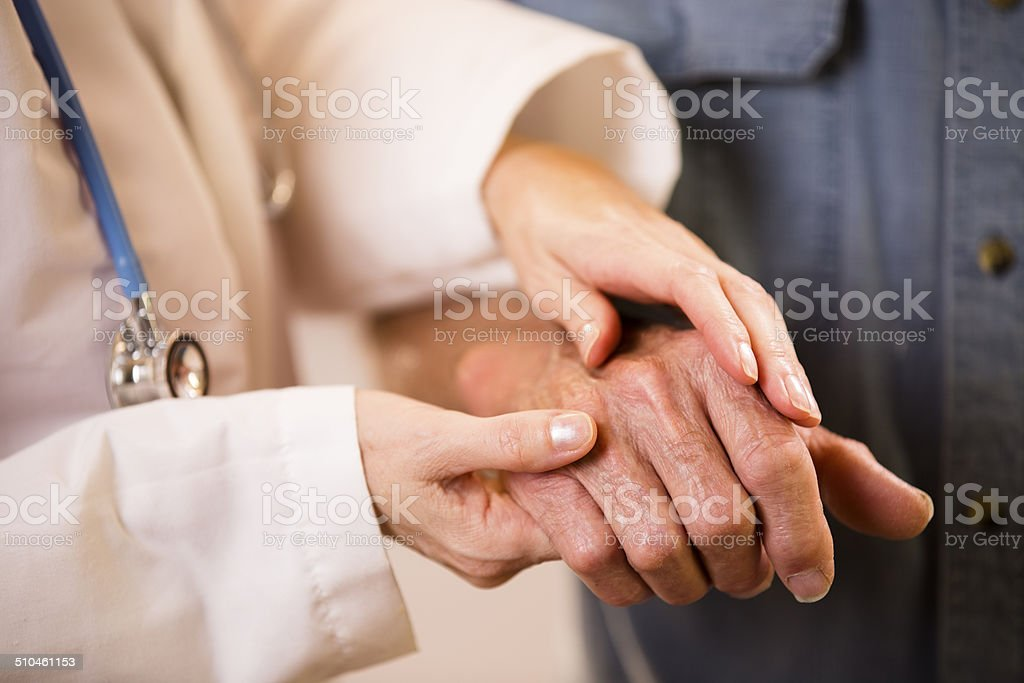 Female doctor helps senior man patient. Holding his hand. stock photo