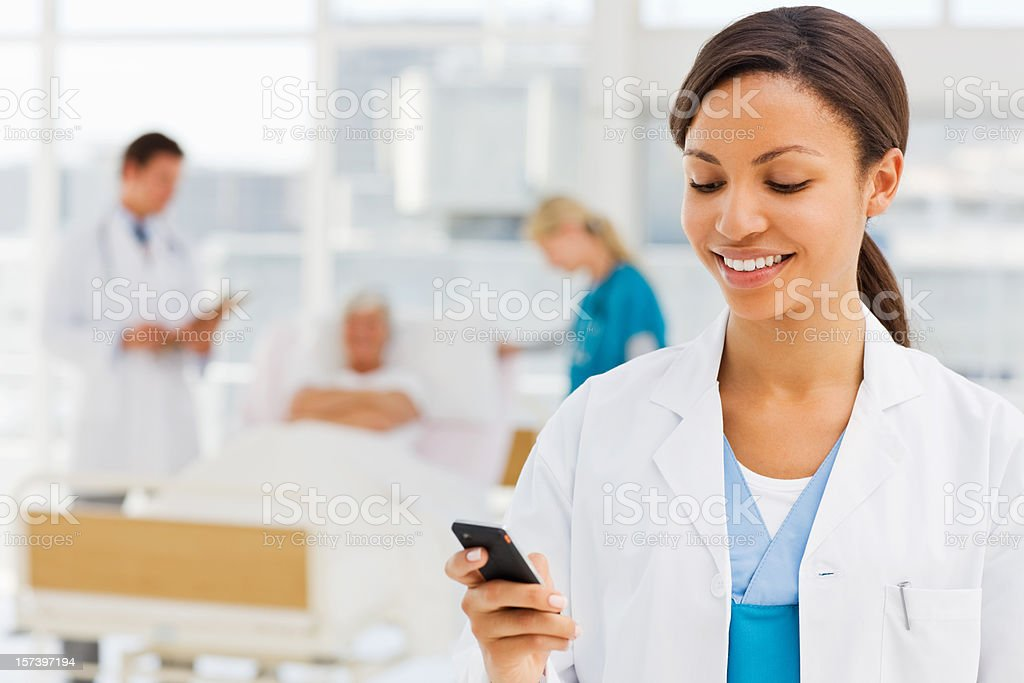 Female doctor holding cellphone stock photo