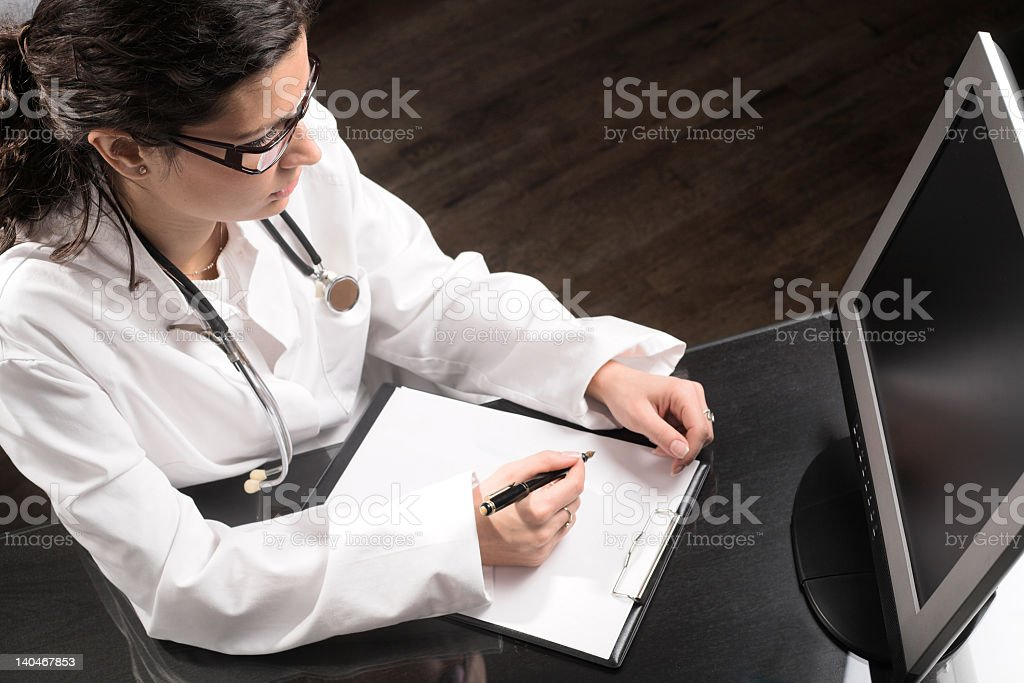 Female doctor in front of computer writing on a clipboard royalty-free stock photo