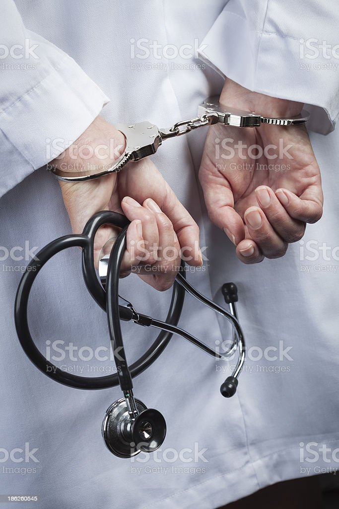 A female doctor in handcuffs and holding a stethoscope royalty-free stock photo