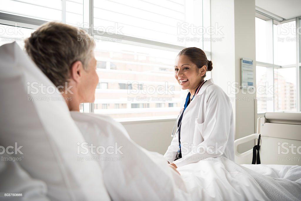 Female doctor in hospital consulting with senior patient stock photo