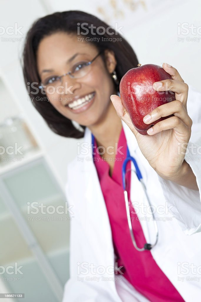 Female Doctor in Office Holding Out Red Apple royalty-free stock photo