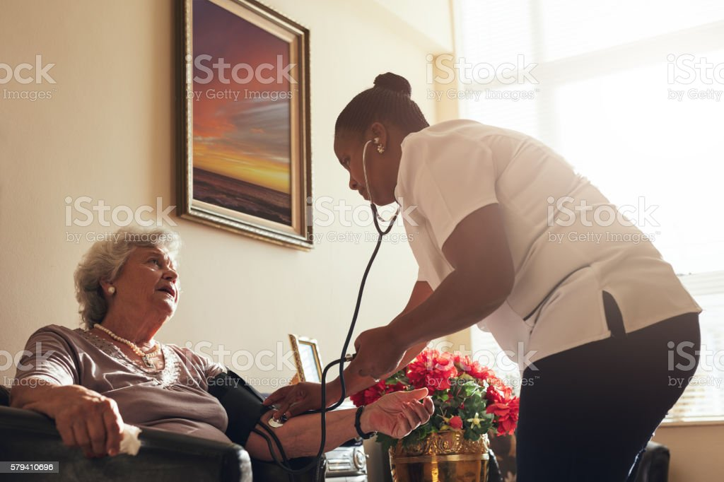 Female doctor measuring blood pressure of old lady stock photo