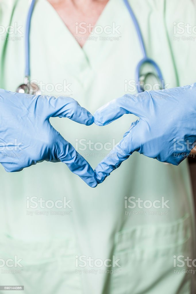 Female doctor or nurse makes 'heart' shape with gloved hands. stock photo