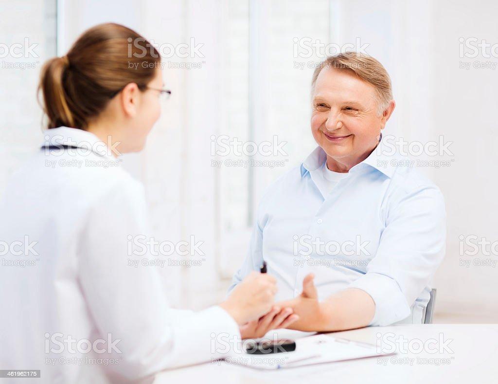 female doctor or nurse measuring blood sugar value stock photo