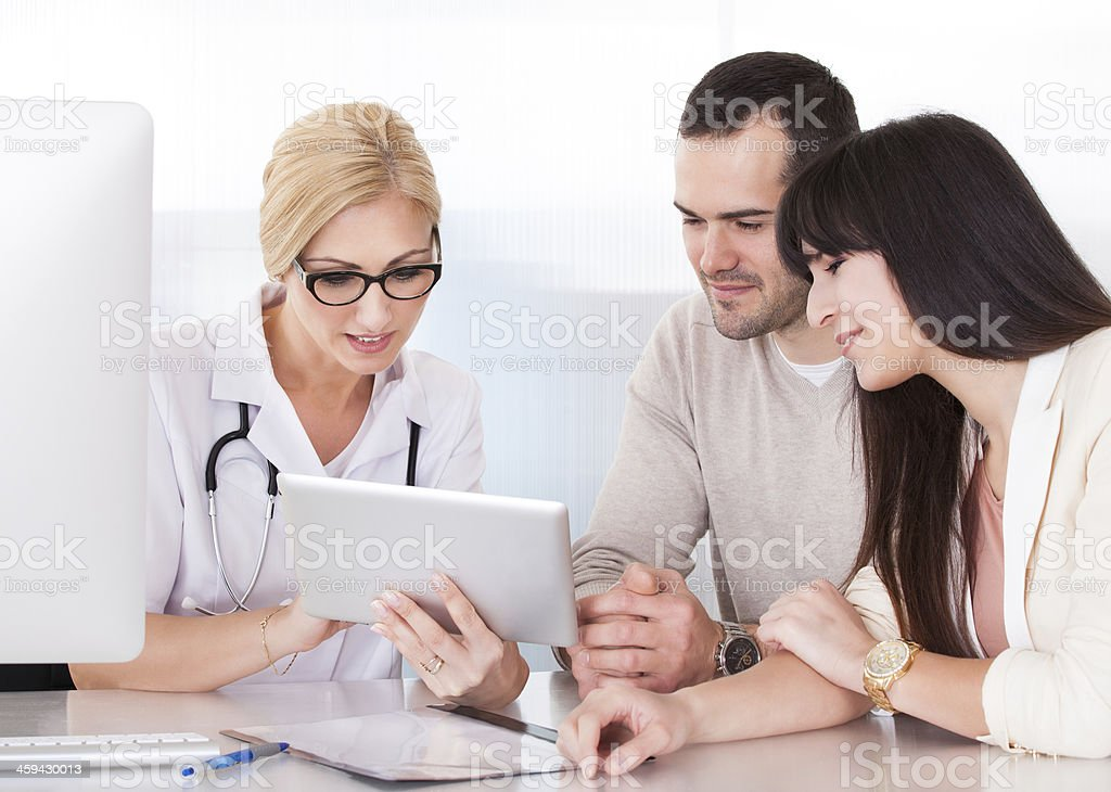 Female doctor showing a couple something on digital tablet royalty-free stock photo
