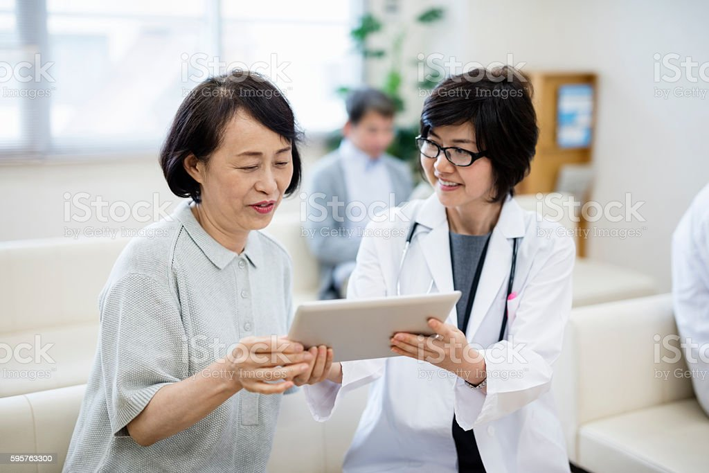 female Doctor showing digital tablet to patient in hospital stock photo