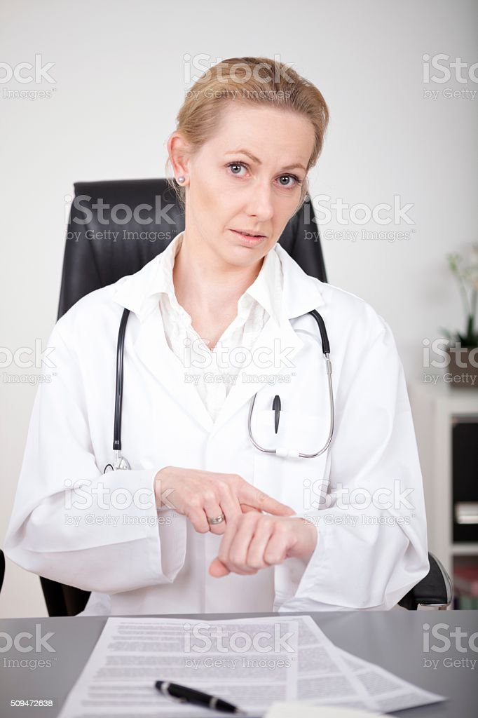 Female Doctor Showing What is the Time Gesture stock photo