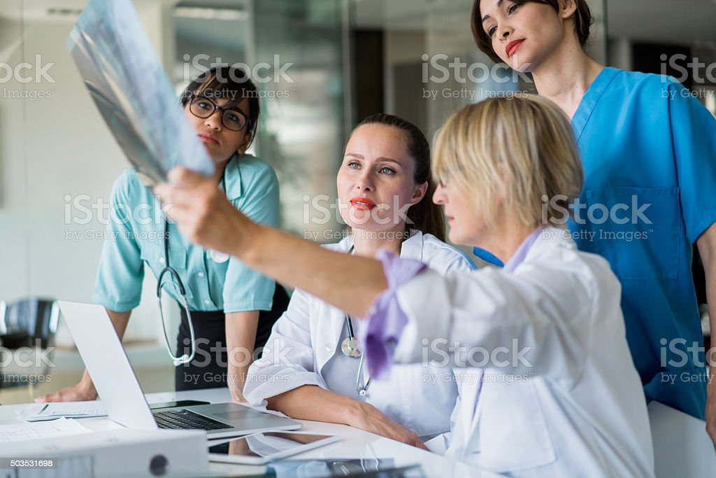 Female doctor showing x-ray to team stock photo