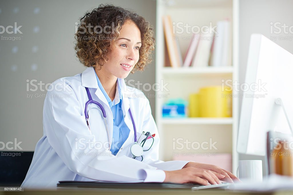 female doctor sitting at her desk stock photo