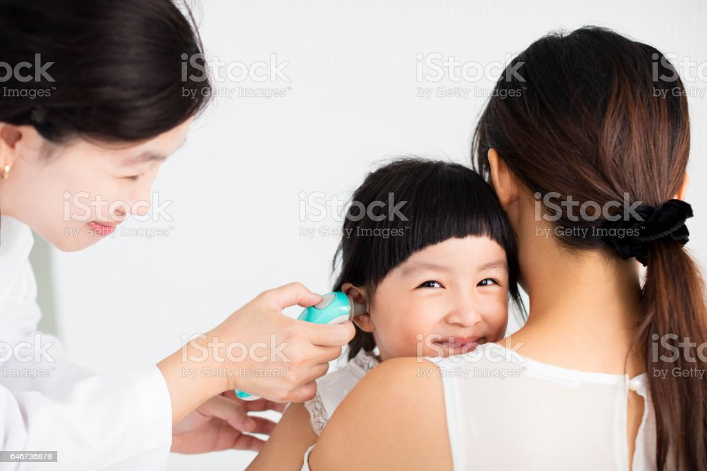 female doctor Taking temperature using in ear thermometer stock photo