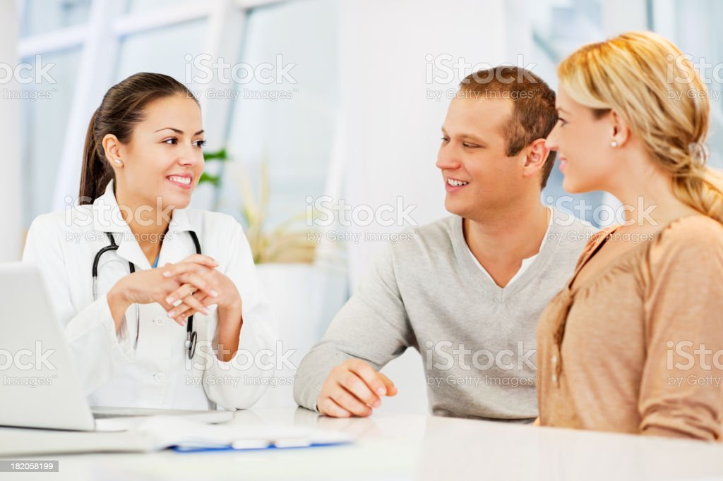 Female doctor talking to a couple. stock photo