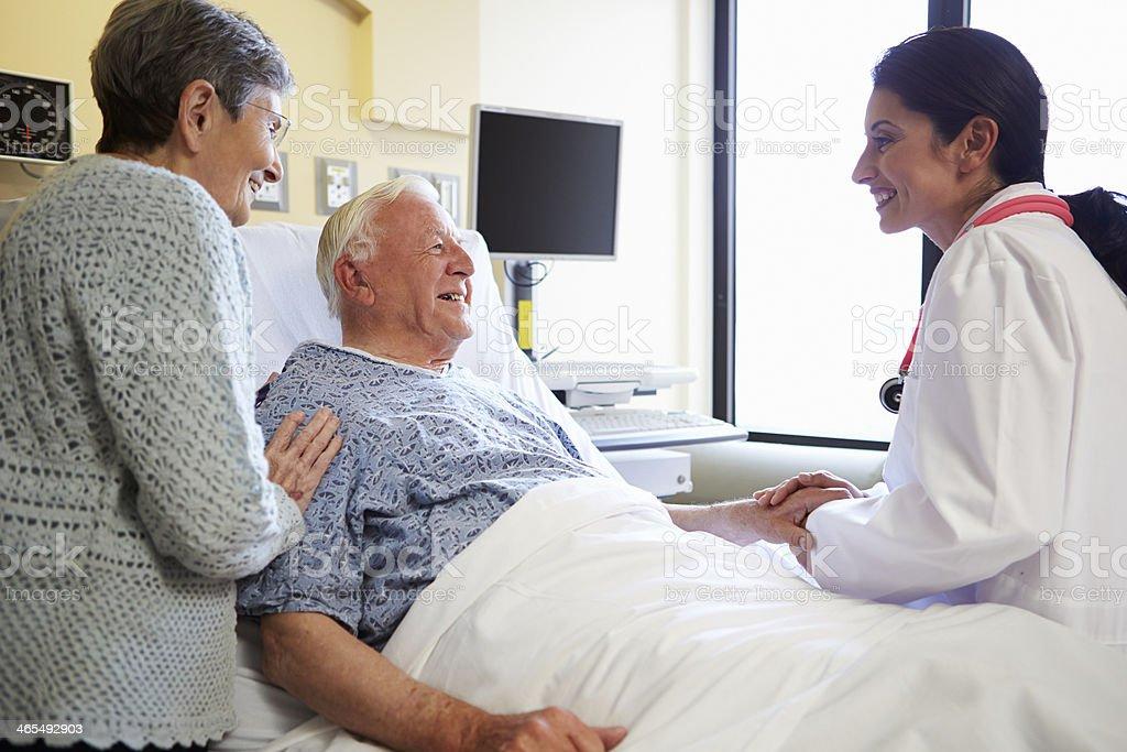 Female Doctor Talking To Senior Couple In Hospital Room stock photo