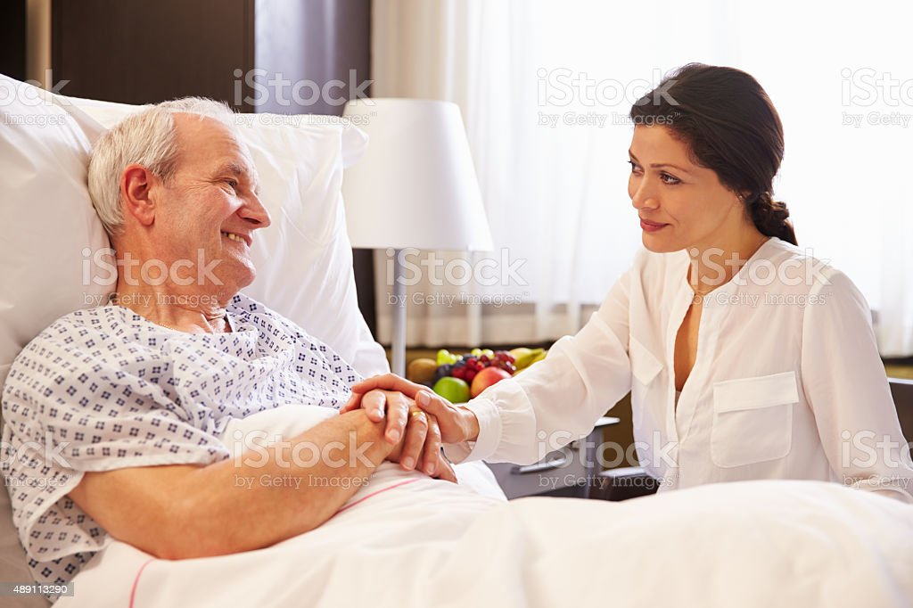 Female Doctor Talking To Senior Male Patient In Hospital Bed stock photo