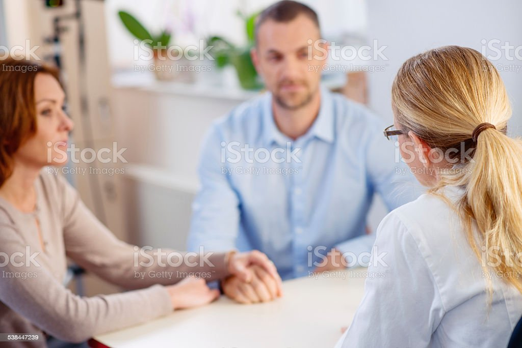 Female Doctor Talking with Mid Adult Couple stock photo