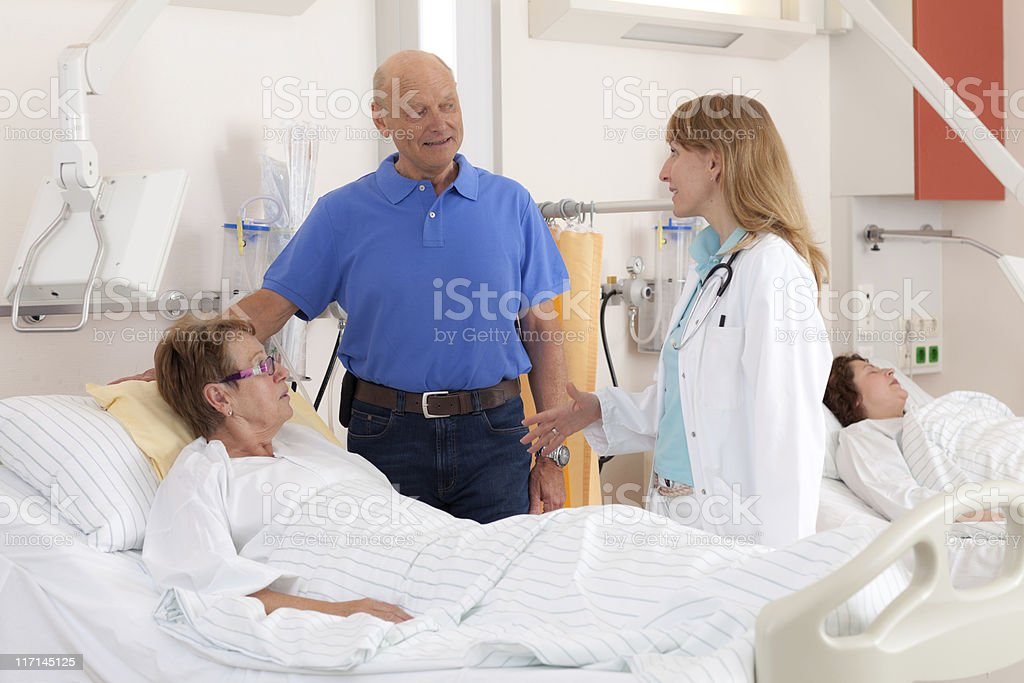 female doctor talking with patient and visitor stock photo