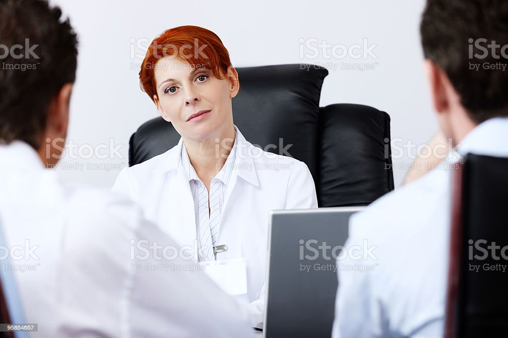female doctor talking with two male patients in modern office stock photo