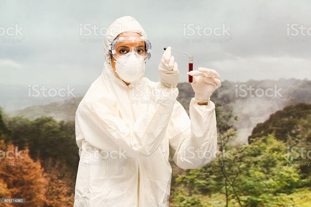 Female doctor testing blood with test tube outdoors stock photo