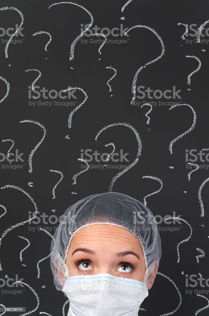 Female doctor thinking in front of question marks royalty-free stock photo