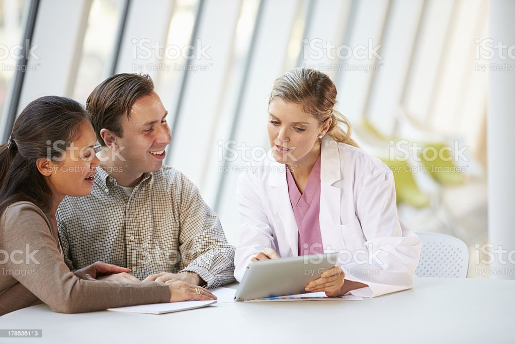 Female Doctor Using Digital Tablet Talking With Patients stock photo