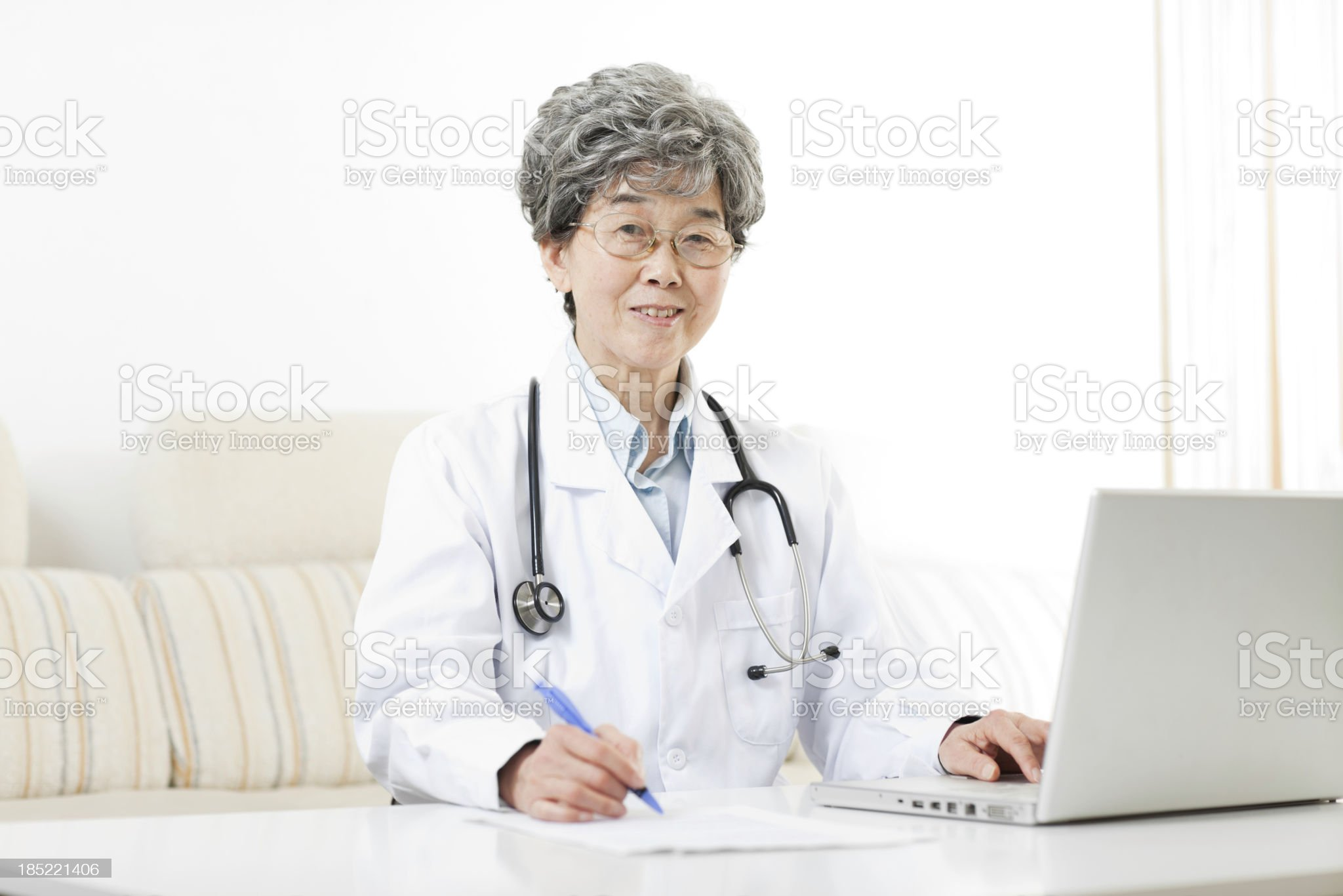 Female doctor using laptop, filling form royalty-free stock photo