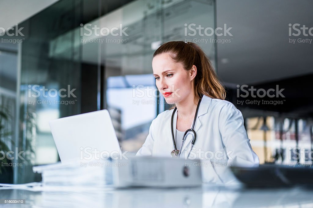 Female doctor using laptop in clinic stock photo