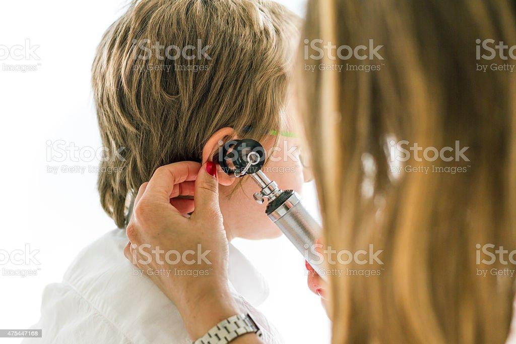 Female doctor using otoscope on child stock photo