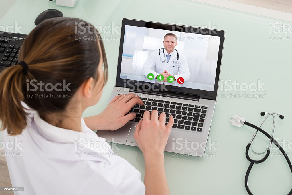 Female Doctor Video Chatting On Laptop stock photo