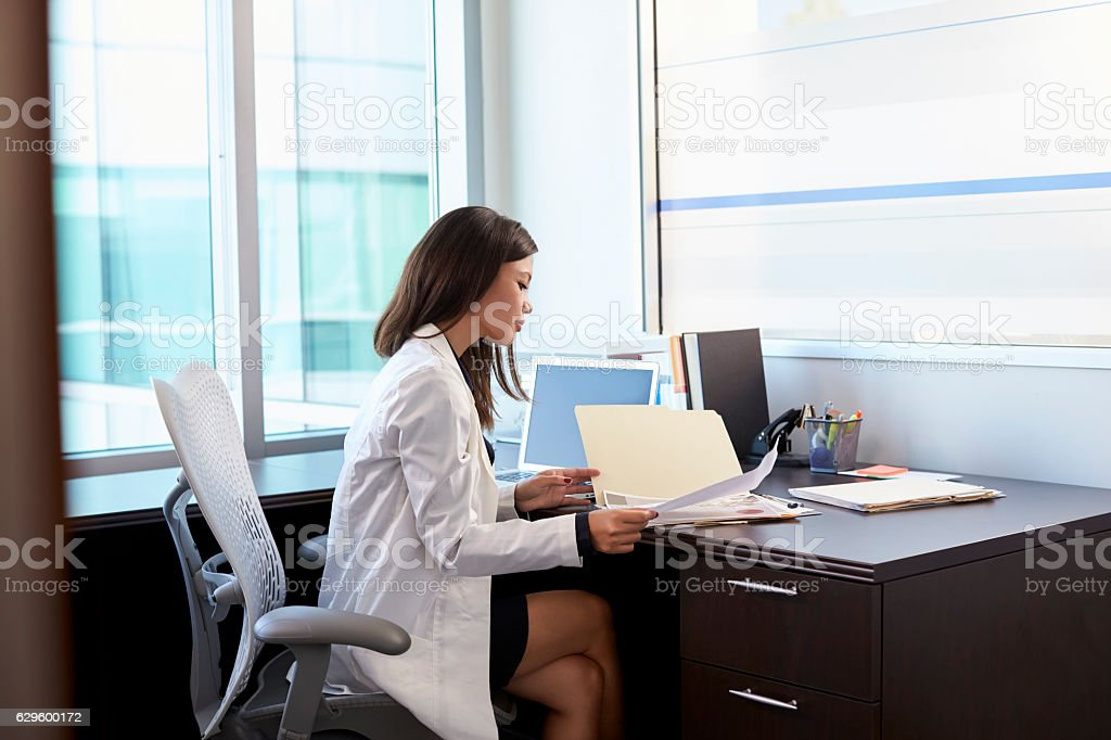 Female Doctor Wearing White Coat Reading Notes In Office stock photo
