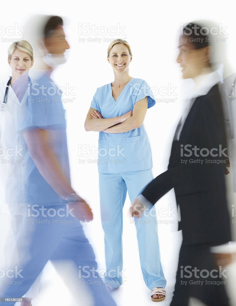 Female doctor with blur view of colleagues walking on white royalty-free stock photo