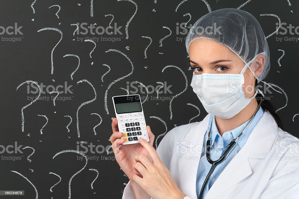 Female doctor with calculator in front of question marks royalty-free stock photo