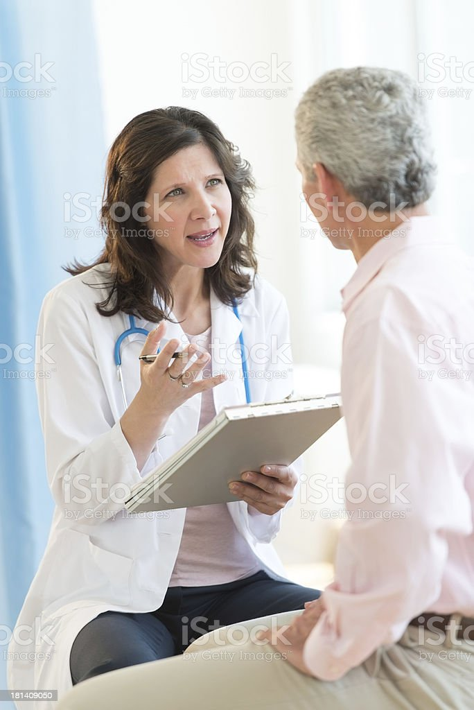 Female doctor with clipboard talks to an adult stock photo