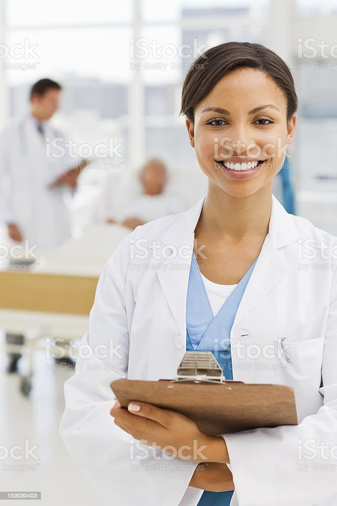 Female doctor with colleague and patient in background royalty-free stock photo