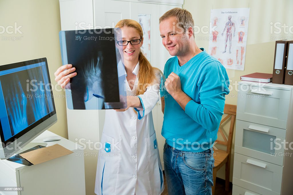 Female doctor with male patient looking at x-ray stock photo