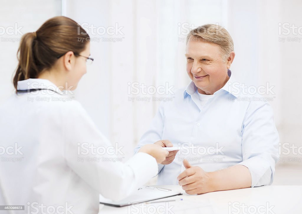 female doctor with old man giving prescription royalty-free stock photo