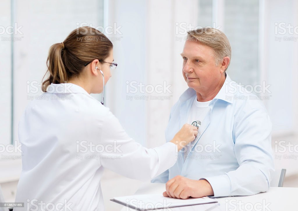 female doctor with old man listening to heart beat stock photo
