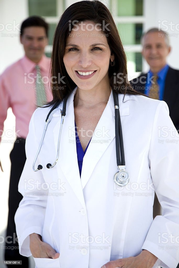 Female doctor with two businessmen in background stock photo